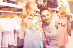 Portrait of  woman and girl shopping kids apparel in clothes sto Stock Photo