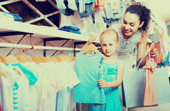 Portrait of  woman and girl shopping kids apparel in clothes sto Royalty Free Stock Photos