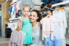 Portrait of  woman and girl shopping kids apparel in clothes sto Stock Photos