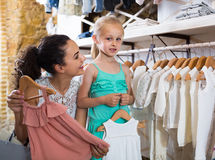 Portrait of  woman and girl shopping white baby apparel in cloth Royalty Free Stock Images