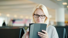 Portrait of a woman in glasses. Sits in the waiting room of the bus station, uses a tablet.  stock video