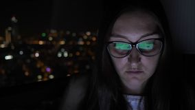 Portrait of woman in glasses working on computer near the window with cityscape. Portrait of young brunette woman in glasses working on computer near the window stock video footage