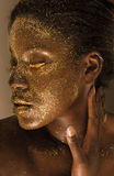 Golden Goddess. A portrait of a woman with gold eyelashes and gold glitter on her face Royalty Free Stock Images