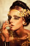 Portrait of woman with golden body art. Goddess Isis stock image