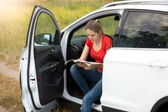 Portrait of young woman got lost on countryside road in car looking for correct route in the map. Portrait of woman got lost on countryside road in car looking Stock Image