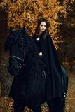 Portrait of a woman in a gothic dress in a Friesian stallion. Portrait of a woman girl in a gothic dress in a Friesian stallion royalty free stock image