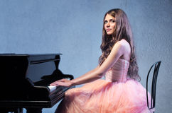 Portrait of woman with grand piano Stock Photo