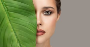 Portrait of woman and green leaf. Organic beauty. stock image
