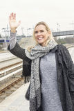 Portrait of woman greeting someone at train station Stock Images