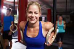 Portrait Of Woman In Gym Exercising With Gymnastic Rings Stock Photo