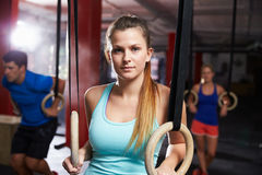 Portrait Of Woman In Gym Exercising With Gymnastic Rings Royalty Free Stock Image