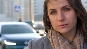 Portrait of a woman with a hairstyle and neutral makeup on a city background closeup stock video