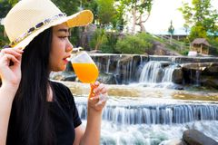 Portrait women hand holding Freshly squeezed orange juice in glass with Waterfall Background royalty free stock photo