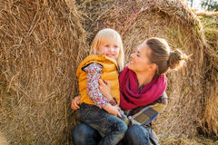 Portrait of woman and happy child sitting on hay on farm Stock Photos