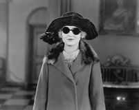 Portrait of woman in hat, sunglasses and coat Royalty Free Stock Photo