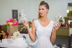 Portrait of woman having difficulties choosing shoes Royalty Free Stock Photos