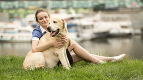 Portrait of a woman with her beautiful dog lying outdoors Stock Photography