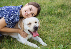 Portrait of a woman with her beautiful dog lying outdoors Royalty Free Stock Photography