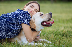 Portrait of a woman with her beautiful dog lying outdoors Stock Images