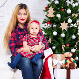 Portrait of woman and her daughter sitting in decorated living r Royalty Free Stock Images