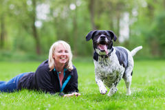 Portrait of a woman with her dog on the meadow Stock Images