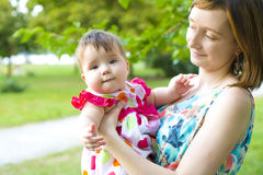 Portrait of a woman with her seven-month daughter. Young mother with the seven-months daughter on hands royalty free stock photo