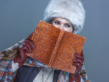 Portrait of woman hiding behind book and looking copy space Royalty Free Stock Photo
