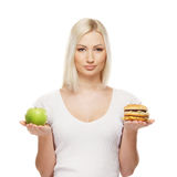 Portrait of a woman holding an apple and a burger Royalty Free Stock Photos