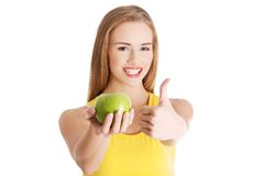 Portrait of woman holding apple showing thumb up Stock Photo