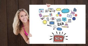 Portrait of woman holding billboard with various icons and text against wooden wall Royalty Free Stock Images