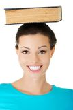 Portrait of a woman holding book on her head Stock Image