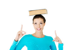 Portrait of a woman holding book on her head Stock Photo