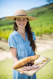Portrait of woman holding bread with cheese and meat on wooden tray Stock Photos