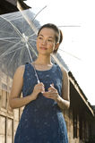 Portrait of woman holding camera. Young woman holding umbrella in her arm Royalty Free Stock Images