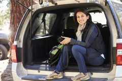 Portrait of woman holding camera in the open back of a car Stock Photography