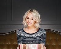 Portrait of a woman holding a Christmas present Stock Images