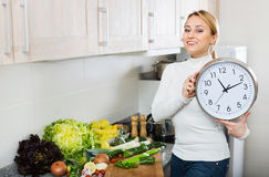 Portrait of woman holding clocks in domestic kitchen Stock Photos