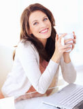 Portrait of woman holding coffee cup by laptop Royalty Free Stock Photo
