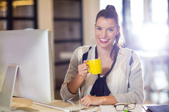 Portrait of woman holding coffee cup in office Royalty Free Stock Photo