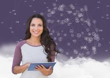 Portrait of a woman holding digital tablet with networking icons and cloud in background. Digital composition of woman holding digital tablet with networking Royalty Free Stock Photography