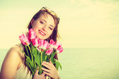 Portrait of woman holding flowers on beach Royalty Free Stock Images