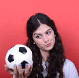 Portrait of woman holding football and looking at it with hate a Royalty Free Stock Photos