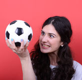 Portrait of woman holding football and looking at it with hate a Stock Image