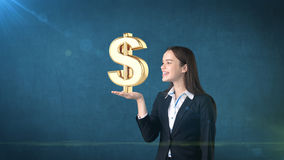 Portrait of woman holding golden dollar sign on the open hand palm, over isolated studio background. Business concept. Portrait of young beautiful longhair Stock Photos