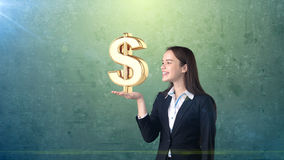 Portrait of woman holding golden dollar sign on the open hand palm, over isolated studio background. Business concept. Portrait of young beautiful longhair Royalty Free Stock Photo