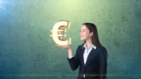 Portrait of woman holding golden euro sign on the open hand palm, over isolated studio background. Business concept. Stock Photo
