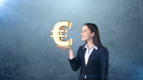 Portrait of woman holding golden euro sign on the open hand palm, over isolated studio background. Business concept. Royalty Free Stock Photo