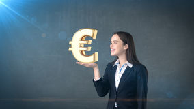Portrait of woman holding golden euro sign on the open hand palm, over isolated studio background. Business concept. Stock Photography