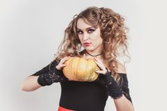 Portrait of woman holding in hands big orange pumpkin isolated on gray background. Wearing black blouse and red skirt. Halloween celebration stock photo