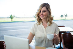 Portrait of woman holding a laptop and coffee cup. Portrait of smiling woman holding a laptop and coffee cup in coffee shop stock photo